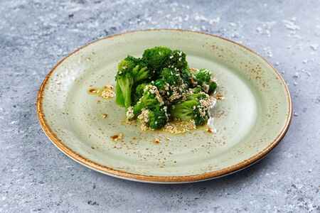 cooked broccoli in a plate on a gray background