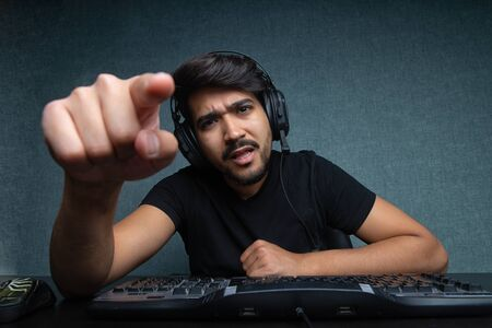 young guy points a finger at a computer screen