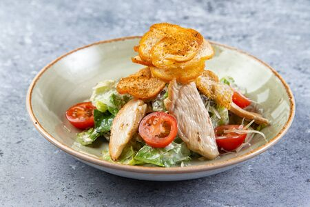 salad with chicken and croutons in a plate on a gray background