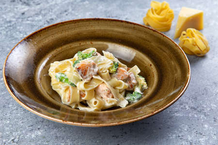 pasta with salmon and herbs in a plate on a gray background Stock Photo