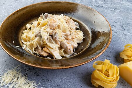 pasta with chicken and mushrooms in a plate on a gray background Banque d'images