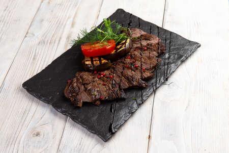 Steak machete on a stone plate. On a light background. Selective focus