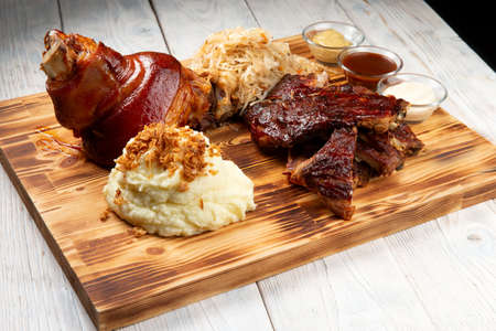 Traditional German beer snacks. Shank, stewed cabbage, fried ribs, mashed potatoes. On a wood panel