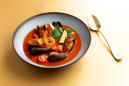 Traditional soup with seafood on a yellow background. Selective focus