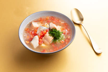 Traditional fish soup on a yellow background. Selective focus