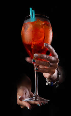 Hands are holding a bright red cocktail. On a dark background. close-up. Selective focus. Standard-Bild