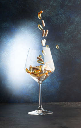 Various vitamins fall into a wine glass. Close-up. selective focus