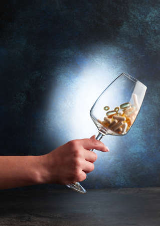 A hand holds a wine glass with various vitamins. Close-up. selective focus Standard-Bild