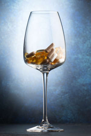 Various vitamins in a wine glass. Close-up. selective focus