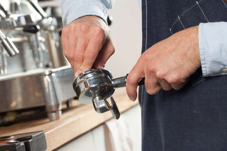 Barista using a tamper to press ground coffee into a portafilter