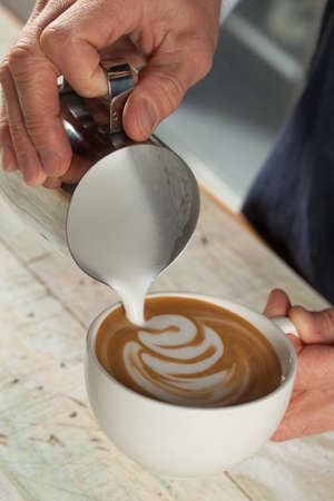Barista making coffee with latte art
