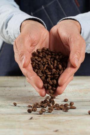 Closeup of a man holding coffe beans, selective focus Standard-Bild