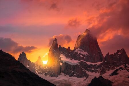 Rocky snowy mountain peaks with the sun rising behind and red clouds. Fritz Rroy in Argentina