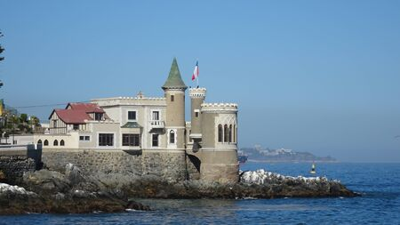 Historic castle in front of the sea with a Chilean flag flying on the tower. Wulff castle in Vi? ? a del Mar in Chile Imagens
