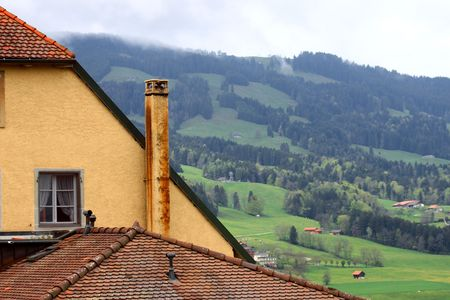 Old tile roof against a mountain landscape Stock Photo