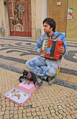 Young beggar musician with small cute dog play accordion and ask for money on street of Lisbon, Portugal on November, 2013