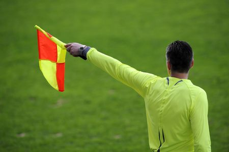 referees: Referee signaling from the sidelines of a soccer game
