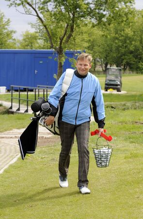 Golf player walk with his club bag and balls Stock Photo