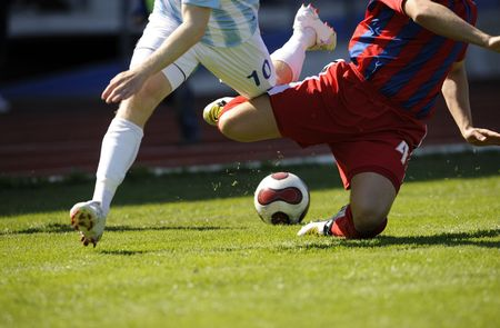 two male soccer players is fighting for the ball