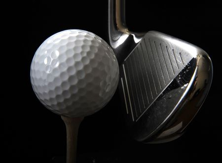 golf club: Golf club with ball on a tee in the black background