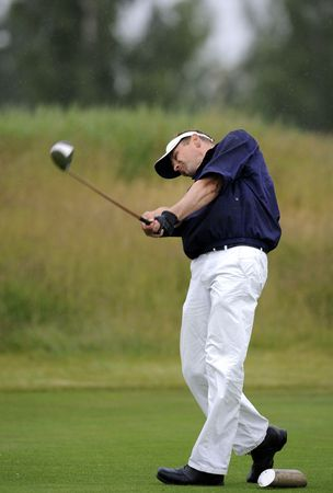 a golfer holding his finish after tee shot Stock Photo