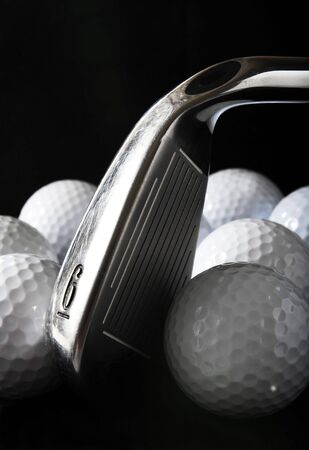 Golf club with golf balls in the black background