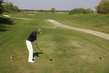 A golfer strikes a golf tee shot