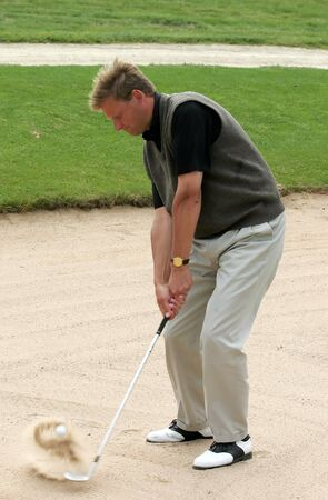 Golf player make a sand-shot Stock Photo
