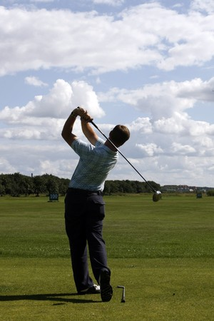 A golfer strikes a tee shot