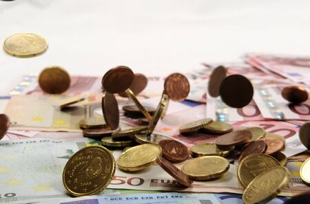 Euro coins falling on euro banknotes, isolated   Stock Photo