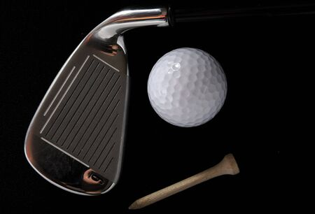 Golf club with ball and tee in the black background