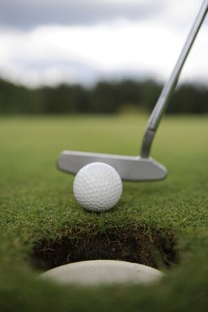 Golf hole with ball and club on green Stock Photo