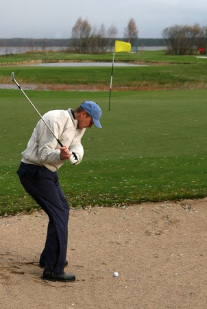Golfer hitting the ball out of the sand bunker straight onto the green.
