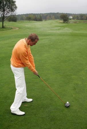 A golfer strikes a tee shot   Stock Photo