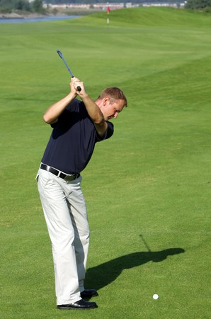 A golf player strikes a tee shot  photo