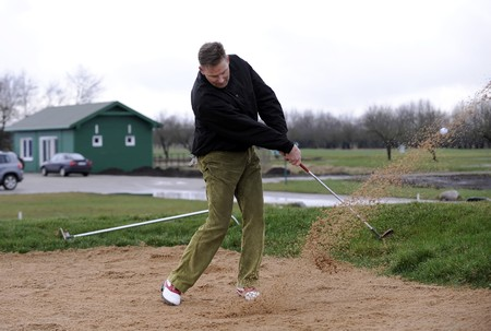 A golfer playing a shot out of a sand-trap with excellent control.