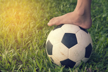 socker: Football and foot on the greed grass. Stock Photo