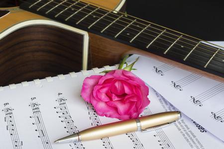 Gitarre mit Stift und Rose auf dem Notizbuch, Vintage-Filter Standard-Bild - 49208618