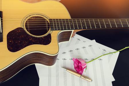 Gitarre mit Stift und Rose auf dem Notizbuch, Vintage-Filter Standard-Bild - 49208626