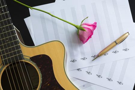 Gitarre mit Stift und Rose auf dem Notizbuch, Vintage-Filter Standard-Bild - 49208629