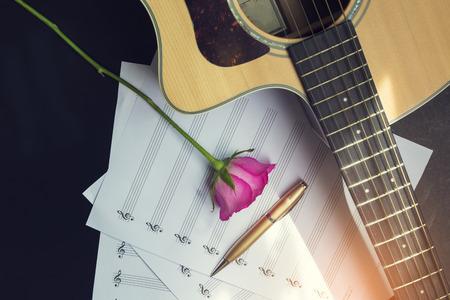 Gitarre mit Stift und Rose auf dem Notizbuch, Vintage-Filter Standard-Bild - 49208630