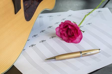 Gitarre mit Stift und Rose auf dem Notizbuch, Vintage-Filter Standard-Bild - 49208632