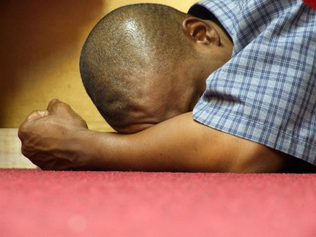 louvor: Intensity - of Worship and Prayer. A black male in intense prayer, stress or contemplation at an all night prayer meeting in a christian church