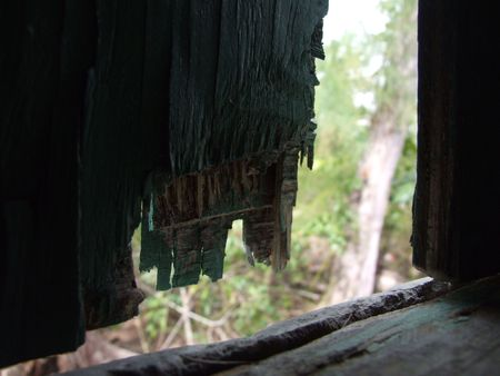 An old weather beaten house window opening after the storms  rain  tornado  hurricanes in the Caribbean photo