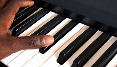 Keyboard player  pianist playing a keyboard  piano during a concert or church worship service.  He is either playing the bassline with his left hand or the melody with his right hand.  photo