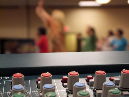 worshipping: Here is a sound mans overlooking view of christians worshipping in church through the sound table. The mixing board is in focus and the worshippers are in the background.