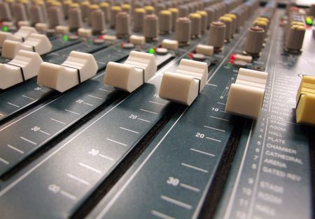 amplified: Here is a sound mans view of a mixing board  console at the sound equipment table of a worship service, conference, or concert. The knobs and slides of the mixing console  board are in focus.