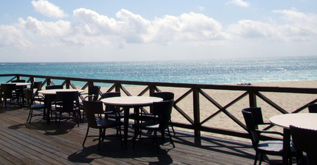 Here are tables and chairs setup for breakfast and lunch at a beach front restaurant - Ocean View photo