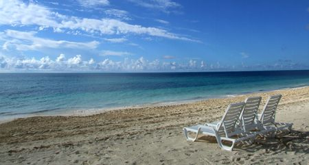 """Aquí está invitando a una imagen con un salón de sillas vacías en una isla tropical playa paraíso. Parece decir: """"Tu lugar en el paraíso está a la espera de usted."""""""
