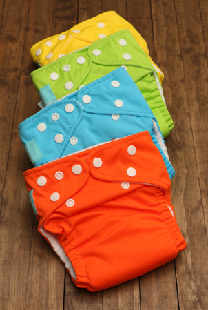 nappies: Four cloth diaper on a wooden background Stock Photo